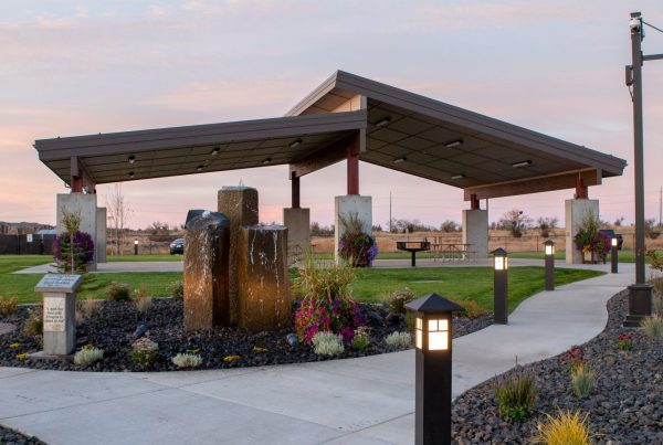 Northern Quest RV Park covered picnic area in background with stone waterfall feature and flowerbeds in foreground at sunrise