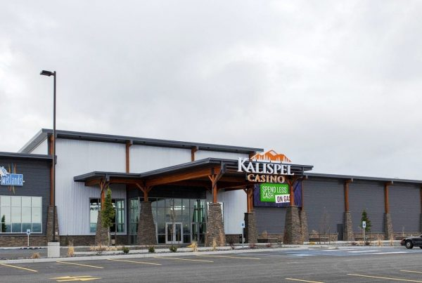 Kalispel Casino exterior wide shot showing the whole front of the building done in northwest elements of stone columns, stone accents, wood beams and gray exterior finishes
