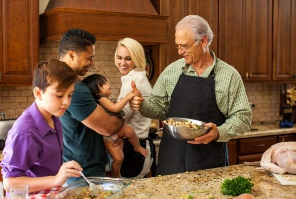 mixed race family in kitchen making Thanksgiving dinner